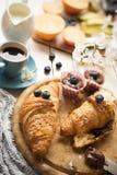 Desayune con los cruasanes, las frutas, el café, los molletes y la goma frescos del chocolate en la tabla de madera blanca Foto de archivo