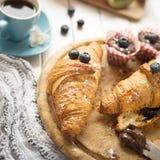 Desayune con los cruasanes, las frutas, el café, los molletes y la goma frescos del chocolate en la tabla de madera blanca Foto de archivo libre de regalías