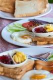 Desayune con los huevos fritos, las salchichas, el cereal, las tostadas y el café Foto de archivo libre de regalías