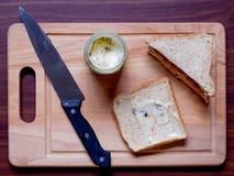 Desayune con pan y la salchicha en la tabla de cortar Foto de archivo