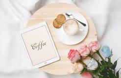 Desayune en cama con capuchino, las rosas y la tableta imágenes de archivo libres de regalías