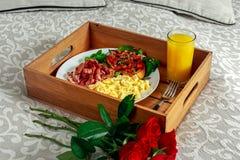 Desayune en cama en la bandeja de madera con el manojo de rosas rojas Huevos de Scrumbled, tocino frito, habas en tostada y ensal Fotos de archivo