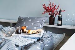 Desayune en cama, una bandeja con queso, grissini, atasco de conos de abeto jovenes, champán y una vela Mañana de la Navidad hone fotos de archivo libres de regalías
