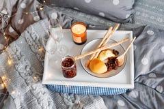 Desayune en cama, una bandeja con queso, grissini, atasco de conos de abeto jovenes, champán y una vela Mañana de la Navidad hone imágenes de archivo libres de regalías