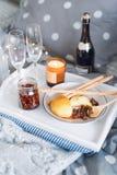 Desayune en cama, una bandeja con queso, grissini, atasco de conos de abeto jovenes, champán y una vela Mañana de la Navidad hone fotografía de archivo
