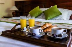 Desayune en la cama para un par con café y cruasanes Fotos de archivo