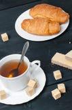 Desayune en la tabla con las galletas, los cruasanes, el azúcar de caña y el té Foto de archivo libre de regalías
