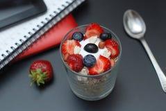 Desayune para la salud, fresas frescas, Blueberies, con la tabla de la oficina del negro de la harina de avena Tableta, ordenador foto de archivo libre de regalías