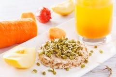 Desayuno útil de productos naturales Granos brotados en una torta soplada del trigo Manzanas y zanahorias frescas, jugo fresco Imagen de archivo