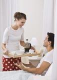 Desayuno atractivo de la porción de la mujer en cama. Imágenes de archivo libres de regalías