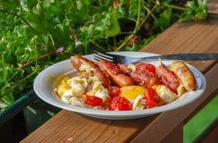 Desayuno austríaco, huevos fritos, salchichas fritas, tomates fritos foto de archivo