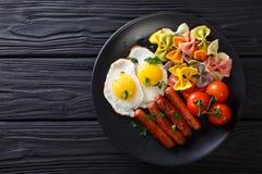 Desayuno caluroso: huevos fritos, salchichas, pastas del farfalle y tomat Fotografía de archivo