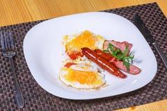 Desayuno cocinado con los huevos fritos, las salchichas, el tocino y el queso Imagen de archivo