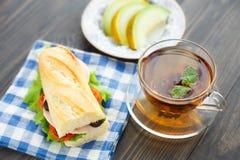 Desayuno con el bocadillo, el té y el melón Imágenes de archivo libres de regalías
