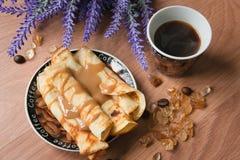 Desayuno con el café y las crepes rematados con la salsa dulce en una tabla de madera fotos de archivo