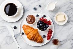 Desayuno con el cruasán con la taza de café Imágenes de archivo libres de regalías
