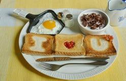 Desayuno con el huevo frito y los copos de maíz Foto de archivo libre de regalías