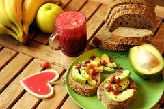 Desayuno con el zumo de fruta y el bocadillo del aguacate Fotos de archivo
