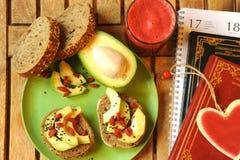 Desayuno con el zumo de fruta y el bocadillo del aguacate Imagen de archivo libre de regalías