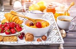Desayuno con la miel y el cruasán de la baya de los copos de maíz Fotos de archivo