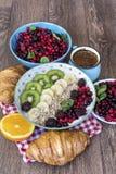 Desayuno con las escamas de la avena, los cruasanes, las frutas del bosque y el café Foto de archivo