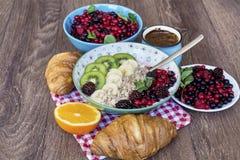 Desayuno con las escamas de la avena, los cruasanes, las frutas del bosque y el café Foto de archivo libre de regalías
