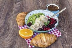 Desayuno con las escamas de la avena, los cruasanes, las frutas del bosque y el café Fotografía de archivo libre de regalías