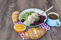 Desayuno con las escamas de la avena, los cruasanes, las frutas del bosque y el café Fotografía de archivo