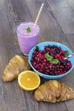 Desayuno con las escamas de la avena, los cruasanes, las frutas del bosque y el smoothie Imagenes de archivo