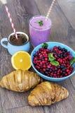 Desayuno con las escamas de la avena, los cruasanes, las frutas del bosque y el smoothie Fotos de archivo