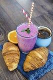 Desayuno con las escamas de la avena, los cruasanes, las frutas del bosque y el smoothie Imágenes de archivo libres de regalías