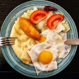 Desayuno con las patatas, el huevo, la chuleta y la ensalada imagen de archivo