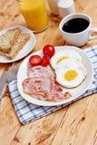 Desayuno con los huevos fritos y el tocino Fotografía de archivo