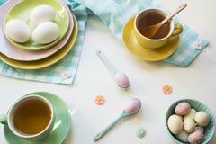 Desayuno con los huevos y el té de Pascua en colores brillantes fotos de archivo libres de regalías