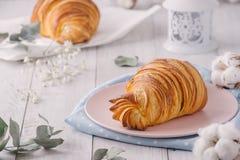 Desayuno continental delicioso con los cruasanes franceses escamosos frescos, cierre para arriba en los cruasanes Con las flores  imagen de archivo