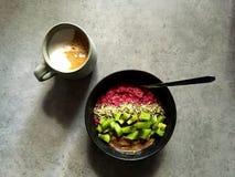 Desayuno: Cuenco del chia de la frambuesa con el kiwi, cañamones, mantequilla de la avellana Fotos de archivo