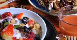 Desayuno de cereales con las bayas, frutas secas, leche metrajes