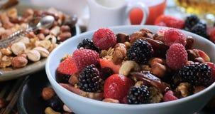 Desayuno de cereales con las bayas, las frutas secas y la leche almacen de video