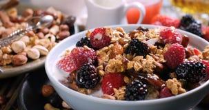 Desayuno de cereales con las bayas, las frutas secas y la leche metrajes