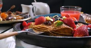 Desayuno de crepes con las bayas y las frutas secas almacen de metraje de vídeo