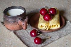 Desayuno de crepes con las cerezas y la leche, aún vida Imagen de archivo