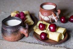 Desayuno de crepes rodadas con las bayas y la leche Imagenes de archivo