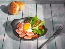 Desayuno de huevos revueltos con las salchichas, tomates y lechuga de hoja en un sart?n negro Servicio en una bandeja de madera d fotos de archivo