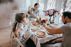 Desayuno de la familia en casa en la cocina acogedora agradable Madre, padre y sus dos hijas comiendo las crepes imagen de archivo