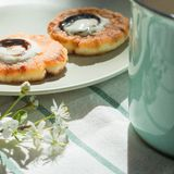 Desayuno de la mañana con las crepes, la taza de la menta y la flor fotografía de archivo