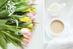 Desayuno de la mañana en primavera con una taza de café sólo con la leche y los pasteles en los colores en colores pastel, un ram Foto de archivo libre de regalías