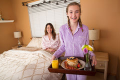 Desayuno de la mamá de la porción del adolescente en cama Foto de archivo