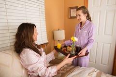 Desayuno de la mamá de la porción del adolescente en cama Fotografía de archivo