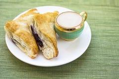 Desayuno de la pasta de hojaldre del zapatero del capuchino y del arándano foto de archivo