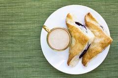 Desayuno de la pasta de hojaldre del zapatero del capuchino y del arándano Fotografía de archivo
